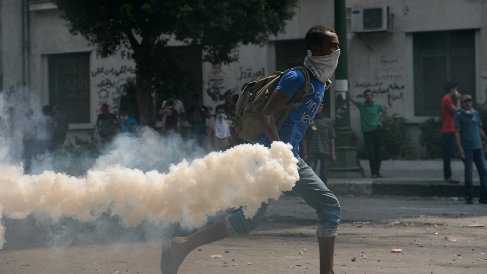 An Egyptian protester throws a tear gas canister at riot police Thursday during clashes near the U.S. Embassy in Cairo.