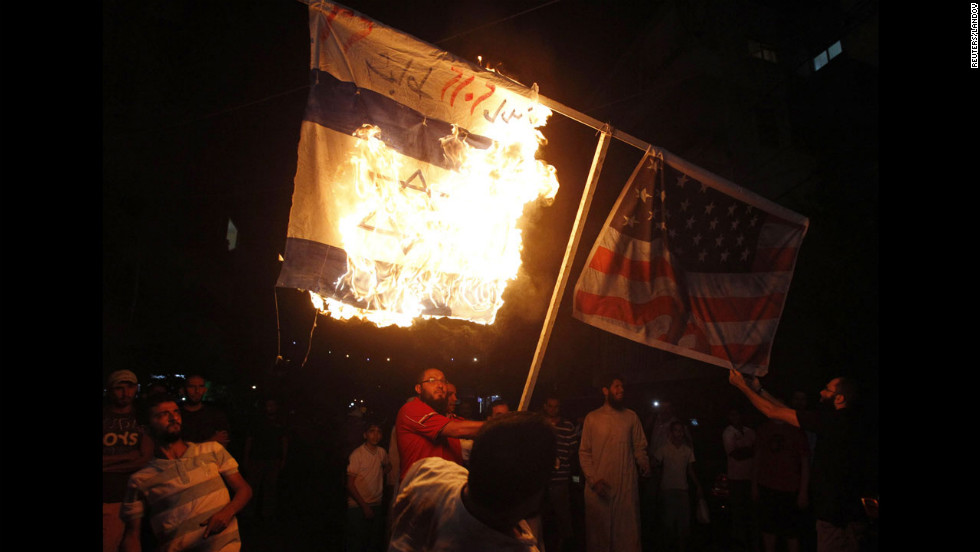 Supporters of Sunni Muslim Salafist leader Ahmad al-Assir burn Israeli and U.S. flags during a protest in Sidon, Lebanon, on Thursday.