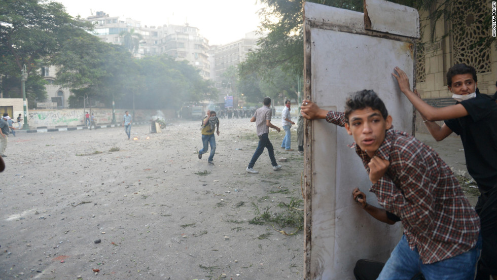Egyptian protesters take cover during clashes with riot police on Thursday.