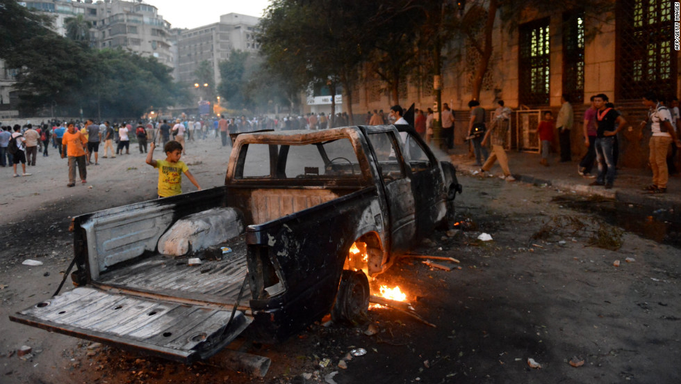 A burned-out pickup sits between Egyptian protesters and riot police in Cairo on Thursday.