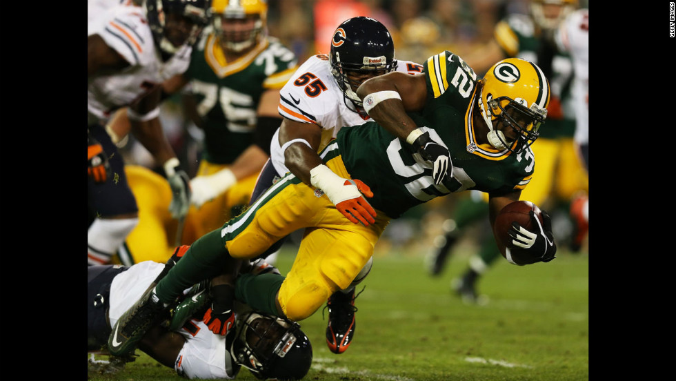 Running back Cedric Benson of the Green Bay Packers is tackled by No. 55 outside linebacker Lance Briggs and No. 21 strong safety Major Wright of the Chicago Bears on Thursday.