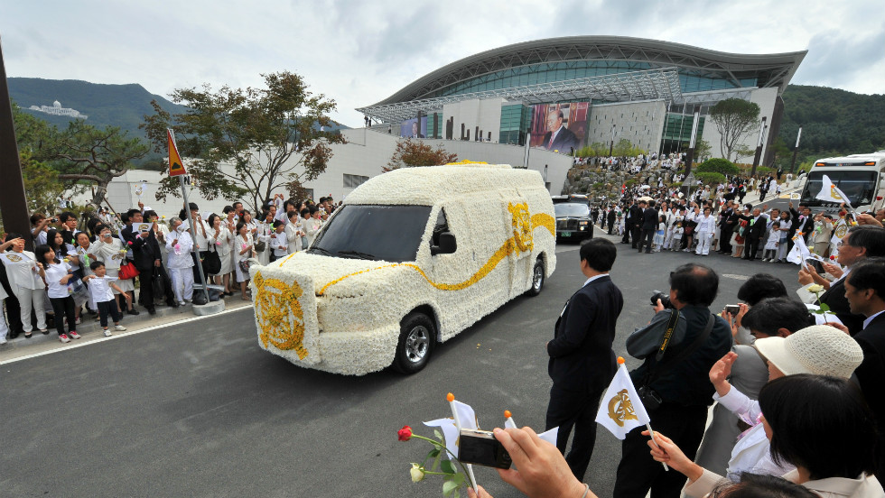 A funeral car carrying Moon's body drives past mourners.