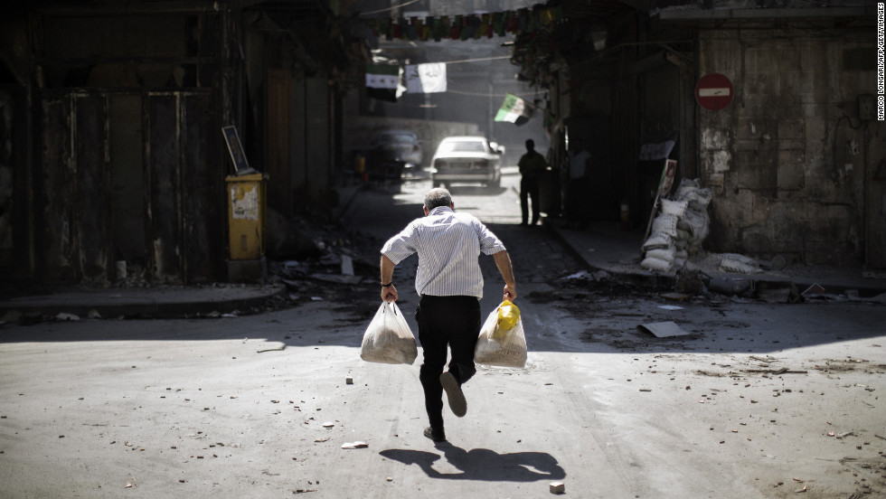 A Syrian man carrying grocery bags tries to dodge sniper fire as he runs through an alley near a checkpoint manned by the Free Syria Army in Aleppo on September 14, 2012.