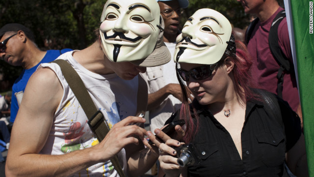 Occupy Wall Street protesters check their cell phones in Washington Square Park, in New York, on Saturday.