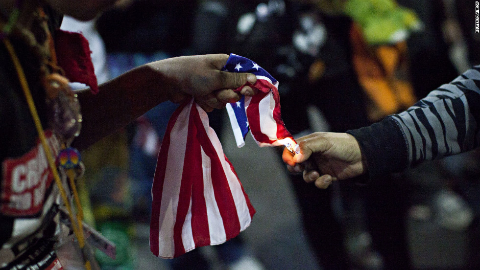 An Occupy Wall Street protester, who said she was not acting as part of the overall Occupy movement but as an individual, lights an American flag on fire during the march in New York City on Saturday.