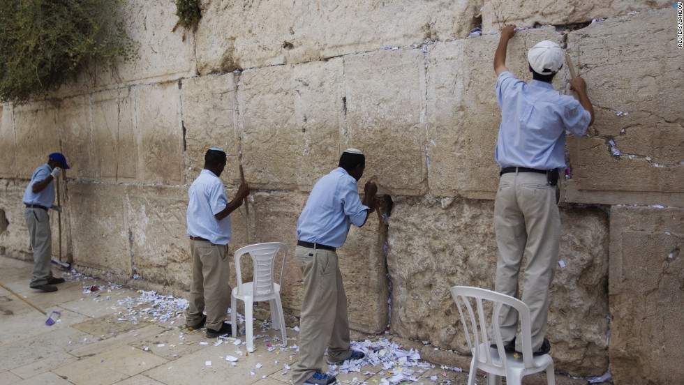Workers remove notes from the cracks of the Western Wall, on Monday, September 9, to make room for more paper notes that Jews believe are notes to God.