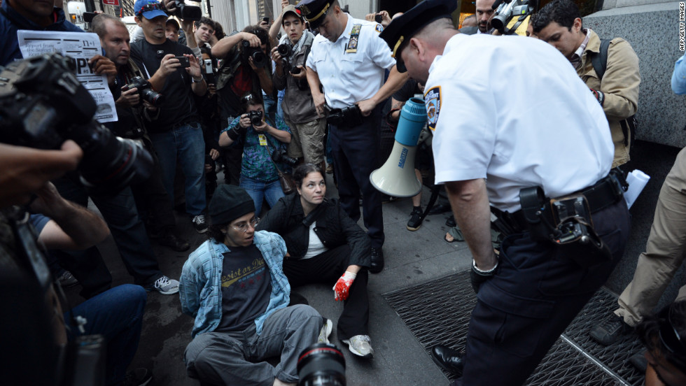 An officer warns people they will be arrested for blocking a sidewalk during the Occupy Wall Street protest on Monday in New York.