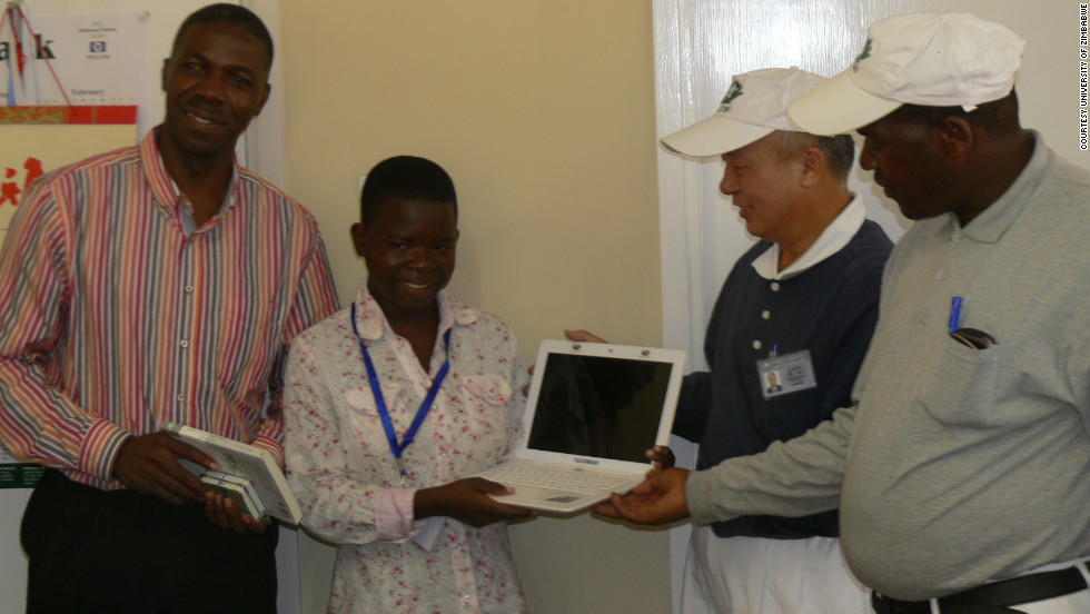 Maud, standing next to Munyaradzi Madambi, the dean of students at the University of Zimbabwe, received last week a donation of a laptop by the TZU CHI Foundation.