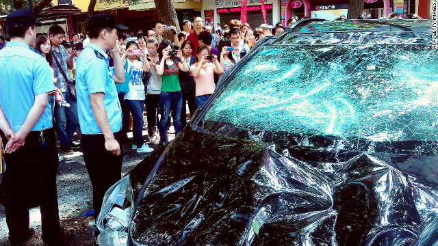 People take pictures of a Japanese car damaged in Xi'an on Saturday.
