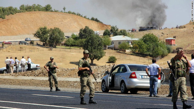 Turkish soldiers stand guard as smokes rises from a bus attacked by members of the PKK on September 18, 2012, in Bingol.