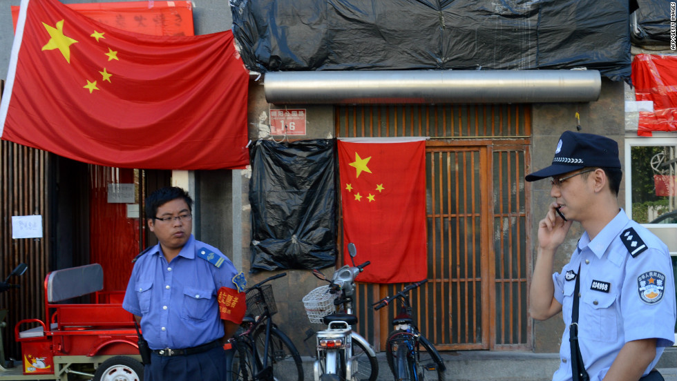 Police walk past a closed Japanese restaurant covered with Chinese national flags as anti-Japanese protests continued outside the Japanese Embassy in Beijing on September 17.