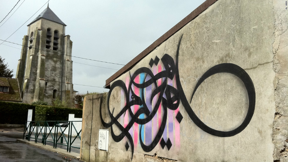 """eL Seed took part in a project to paint on walls in a suburb of Paris called Montry. As he was nearing the end, the owner of the wall, who had agreed to the painting, objected because it was in Arabic. """"I had forgotten the particularly violent brand of French Arabophobia normalized in mainstream culture,"""" said eL Seed on his website. """"For this man, seeing an Arab man paint in Arabic surely scared him.""""A week later, eL Seed returned in defiance and wrote """"Open Your Heart"""" on a public wall nearby."""