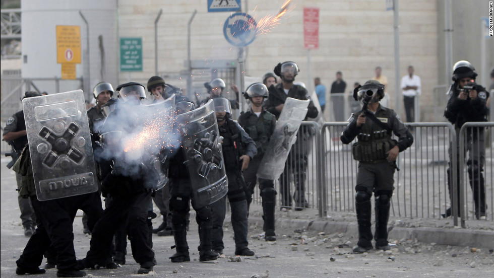 Israeli border policemen fire tear gas toward Palestinian protesters on Tuesday.