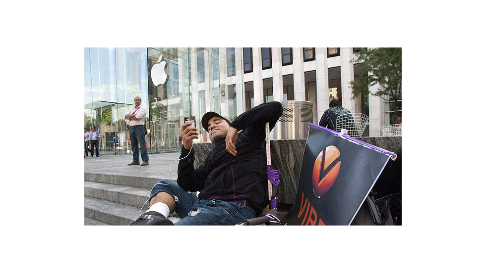 A man waits in line Monday outside the flagship Apple store on 5th Avenue in New York.