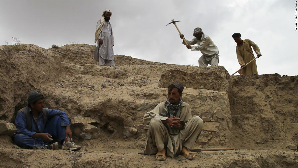 Locals from relocated villages near Mes Aynak remove dirt and rocks to expose buried artifacts.