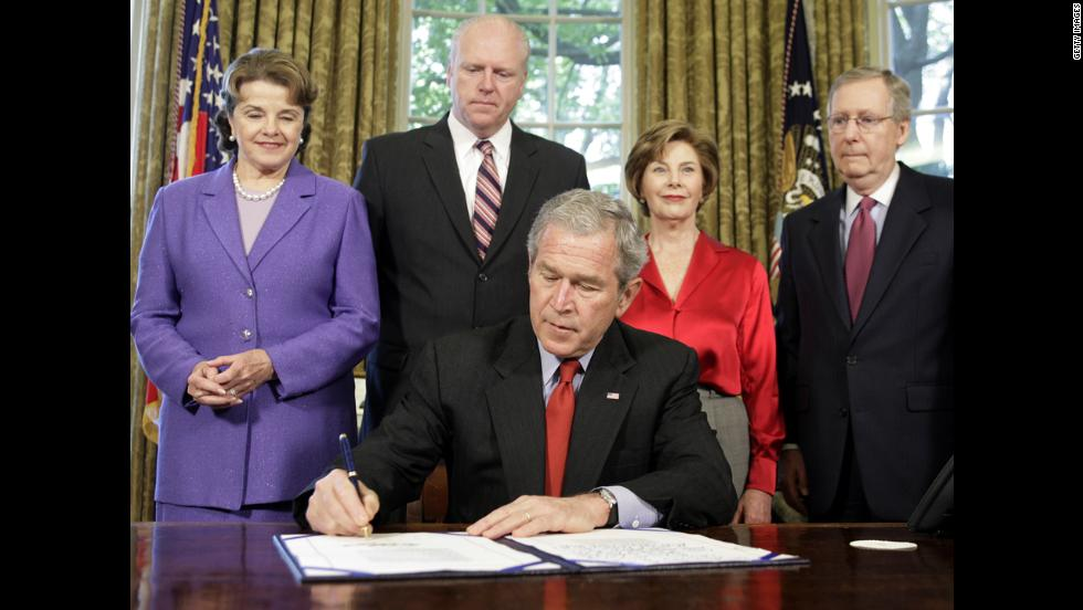 U.S. President George W. Bush signs H.R. 4286, which gave the Congressional Gold Medal in absentia to Suu Kyi, in the Oval Office of the White House on May 6, 2008. From left : California Sen. Dianne Feinstein, U.S. Rep. Joe Crowley of New York, first lady Laura Bush and Kentucky Sen. Mitch McConnell.