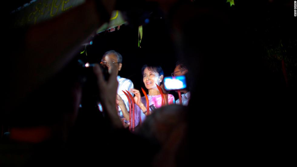 Suu Kyi greets crowds of well-wishers at the gate of her house after her release from house arrest, on November 13, 2010, in Yangon.