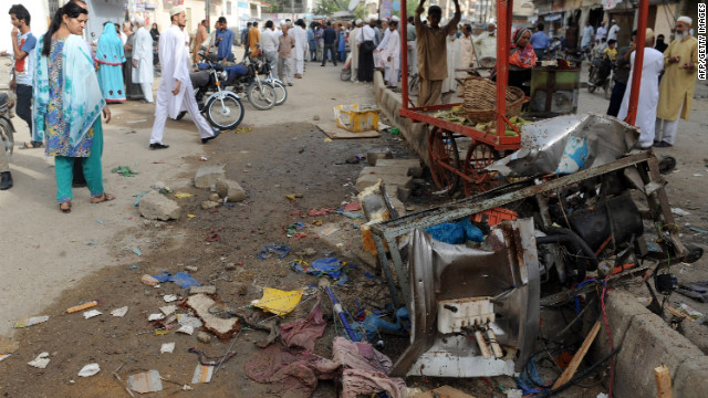 Local residents gather at the site of an overnight bomb explosion in Karachi on September 19, 2012.