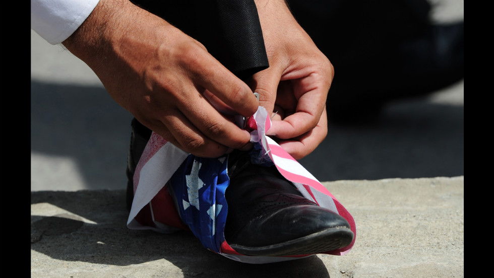 A Pakistani lawyer wraps a U.S. flag onto his shoe in Islamabad on Wednesday.