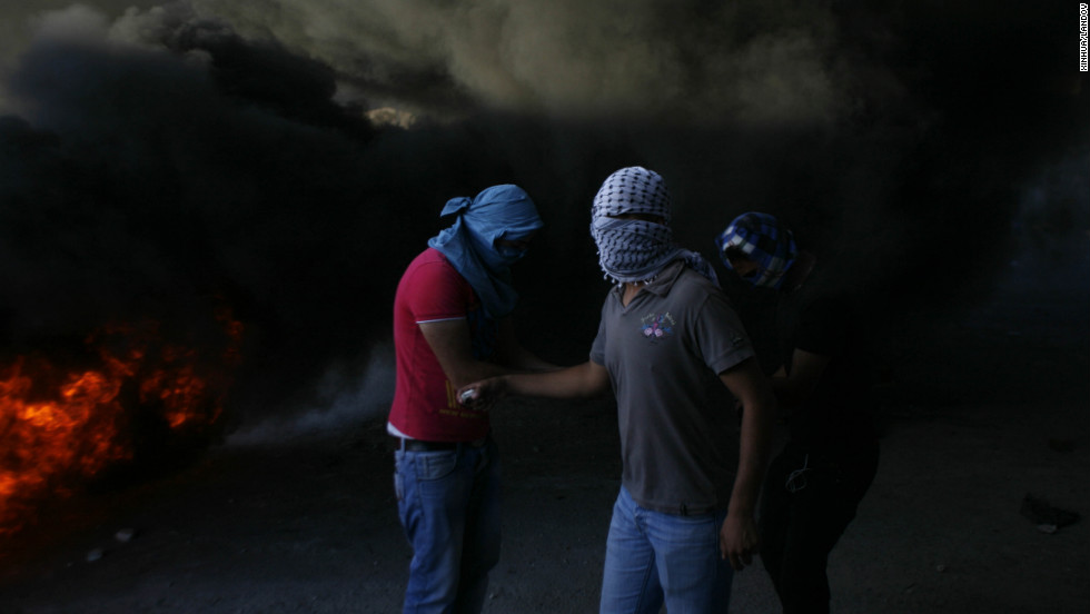 Masked Palestinians are seen during clashes with Israeli security forces in Shuafat refugee camp, Jerusalem, on Tuesday, September 18.