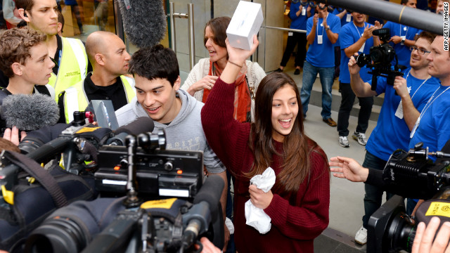 James (centre-L) and Tamsyn Vohradsky (centre-R) hold up their iPhone 5 after becoming the first buyer of Apple's new iPhone 5 from their flagship store in Sydney, on September 21, 2012.  Gadget lovers in Australia were the first to get their hands on the new generation iPhone 5, with the queues snaking around Apple's flagship store in Sydney suggesting another huge hit for the company. AFP PHOTO/William WEST      AFP PHOTO/William WEST        (Photo credit should read WILLIAM WEST/AFP/GettyImages)