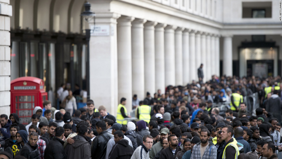 Customers wait outside the Covent Garden in London on Friday. Throngs of shoppers lined up outside Apple stores in Sydney, Tokyo, London, Paris and Munich, among other cities where the phone went on sale.