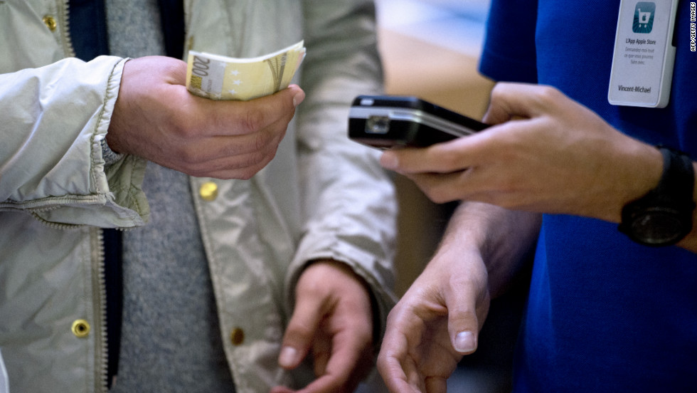 A customer, left, holds euro banknotes to purchase the new phone from an Apple Store employee in France.
