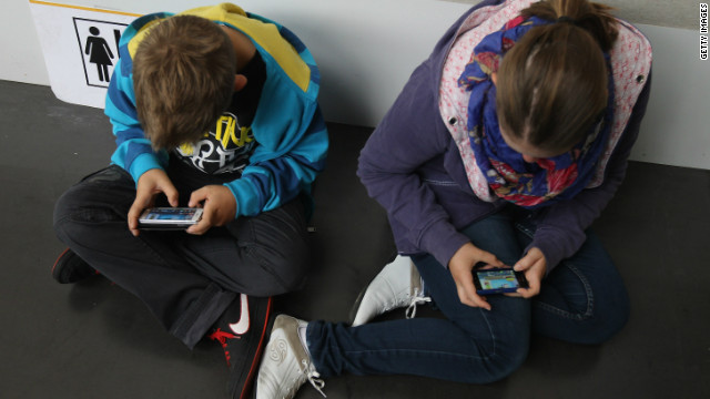 Children play video games on their smartphones.
