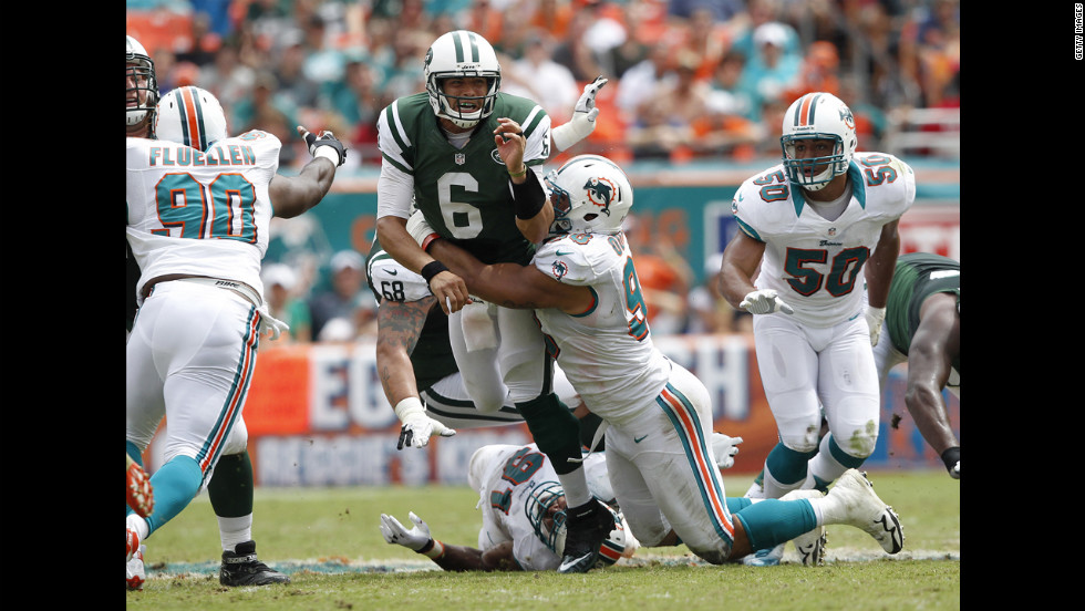 Jared Odrick of the Miami Dolphins hits Mark Sanchez of the New York Jets as he gets the ball away.