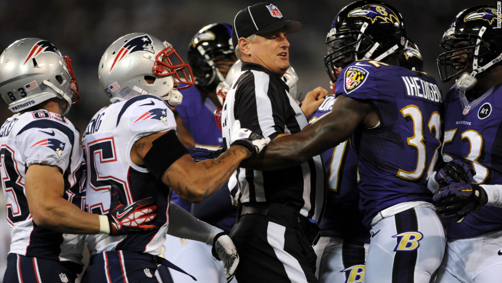 A referee seperates New England and Baltimore players.