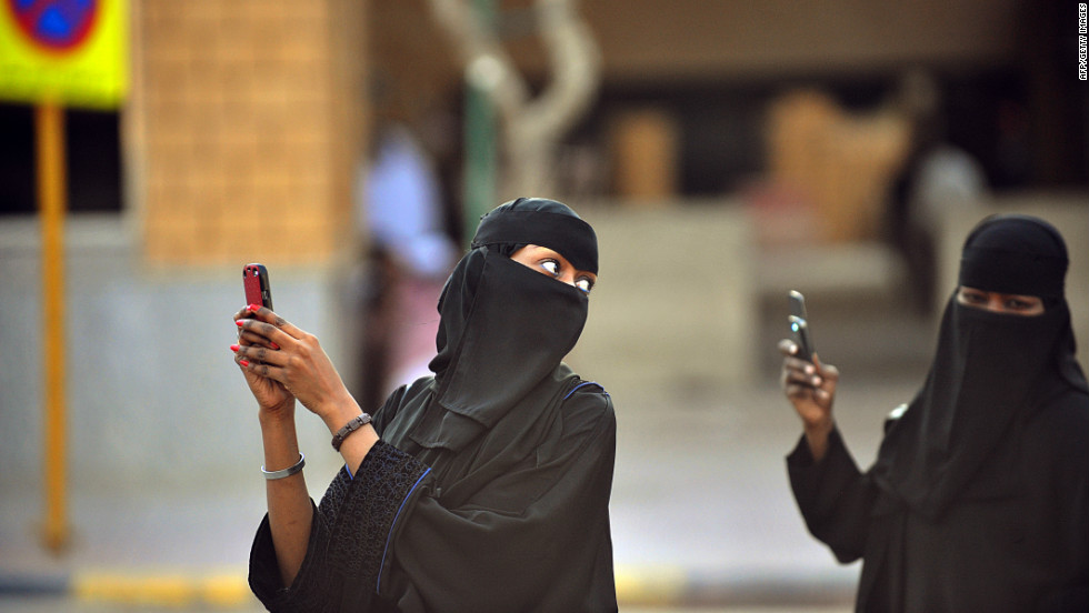 These Saudi women are taking photos with their mobile phones after the end of a prayer performed on the first day of Eid al-Fitr in the great mosque in the old City of Riyadh to mark the end of the holy fasting month of Ramadan.