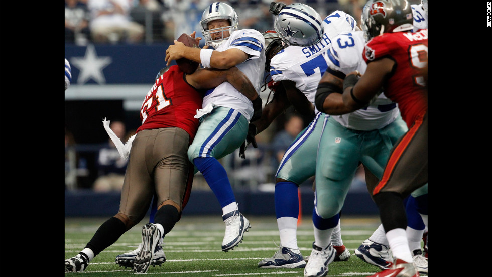Tony Romo of the Dallas Cowboys fumbles the ball Sunday after being hit by Michael Bennett of the Tampa Bay Buccaneers.