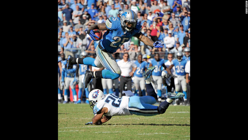 Mikel LeShoure of the Detroit Lions jumps over Ryan Mouton of the Tennessee Titans.