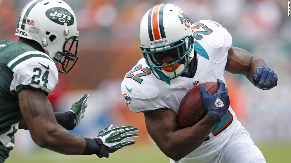 Reggie Bush of the Dolphins runs against the Jets' Darrelle Revis.