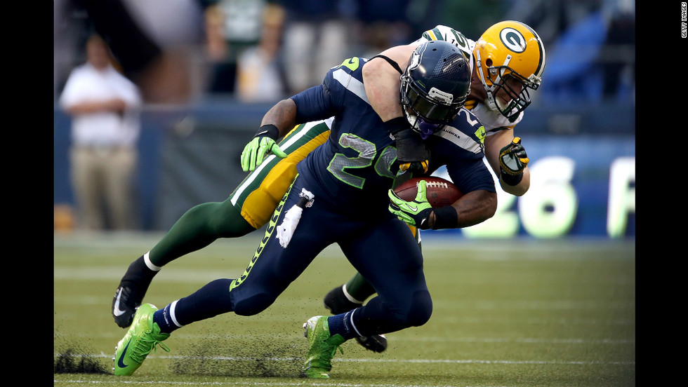 Green Bay's A.J. Hawk tackles Marshawn Lynch of the Seahawks.