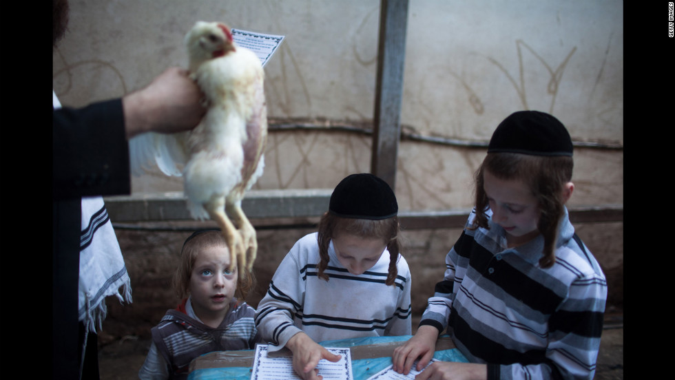 An Ultra-Orthodox Jewish man swings a chicken over his family during the Kaparot ceremony on Thursday, September 20, in Bnei Brak, Israel.