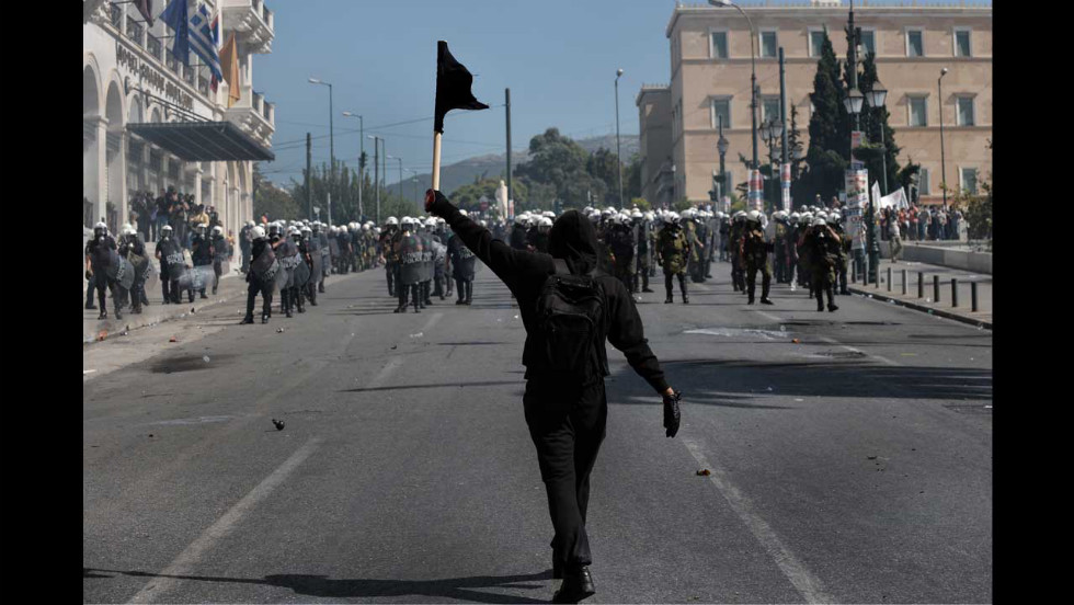 A demonstrator waves a black flag in front of riot police in Athens on Wednesday.
