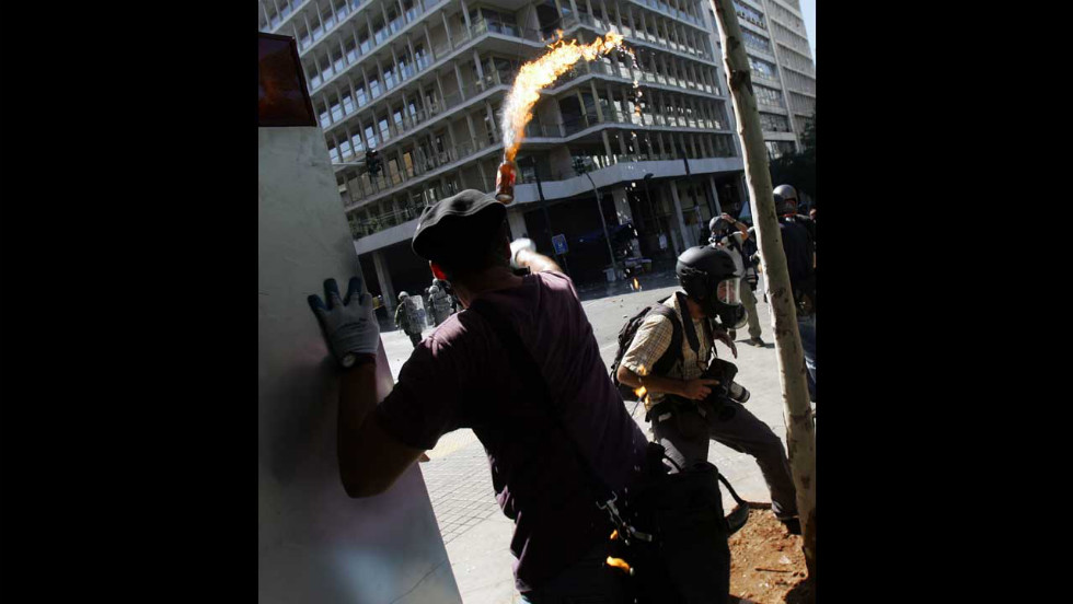 A demostrator throws a Molotov cocktail toward riot police near Syntagma Square in Athens on Wednesday.