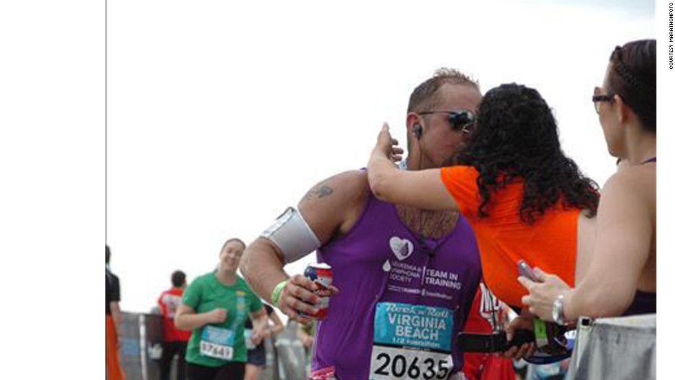 Legg gives his wife, Suzanne, a kiss on his way to the finish line. The beer can in his hand is a tradition that started when he ran marathons as a Navy SEAL.