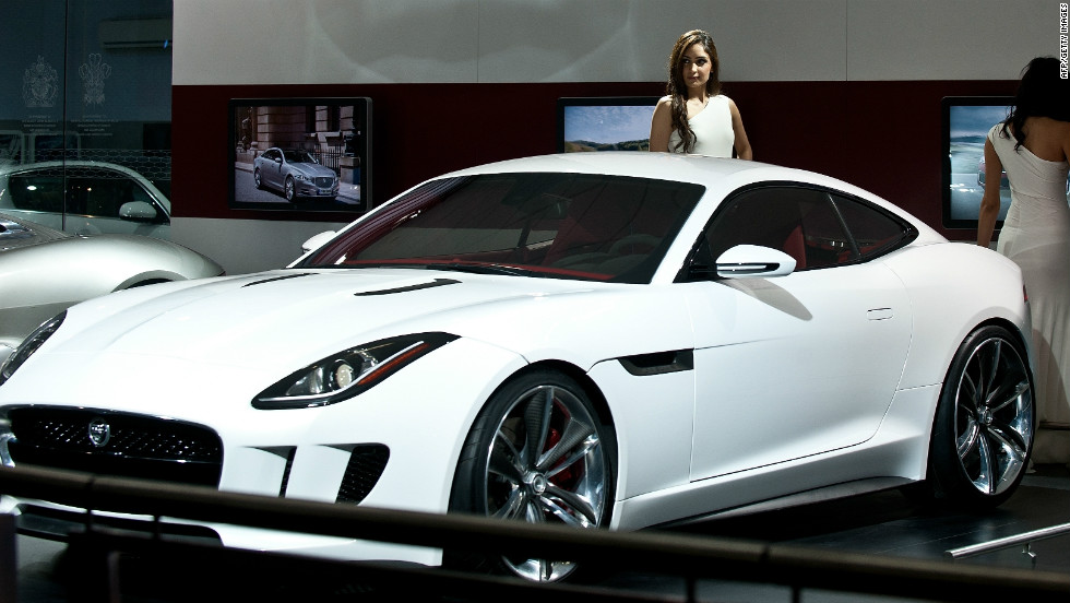 a model with the jaguar cx16 concept car at the 2012 india auto expo in new
