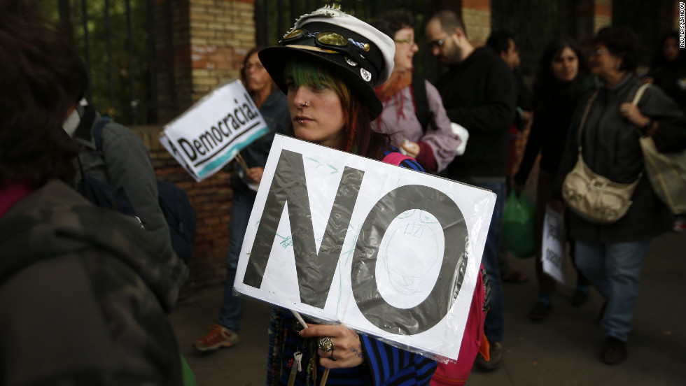 A protester carries a sign as she walks toward the Spanish Parliament to join the demonstration.
