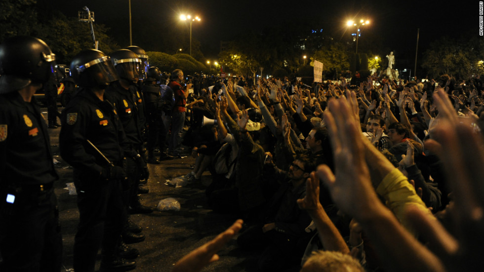 Riot police stand in front of protesters.