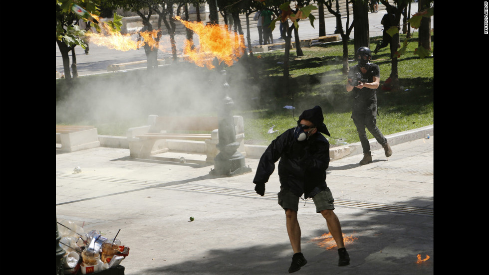 A demonstrator throws a Molotov cocktail at riot police near Syntagma Square on Wednesday.