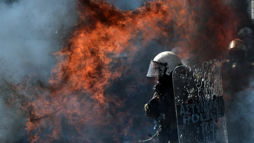 A fire bomb explodes near a riot police squad on Wednesday.