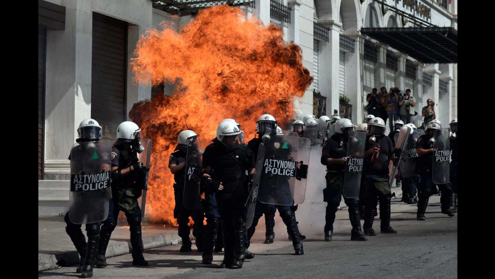 A fire bomb explodes behind a riot police squad on Wednesday.