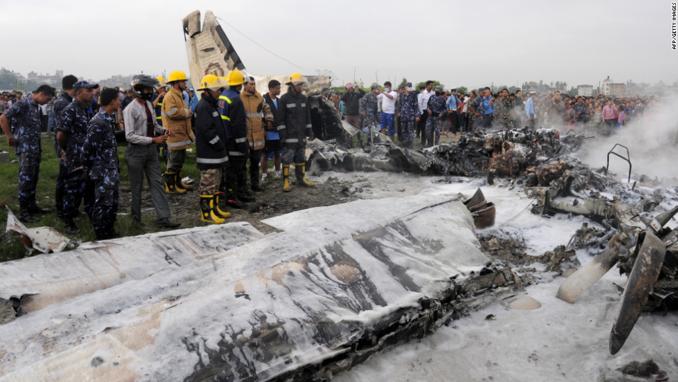 Firefighters and volunteers stand near the wreckage. The plane crashed on the banks of the Manohara River in Bhaktapur District, Nepal's Civil Aviation Authority said.