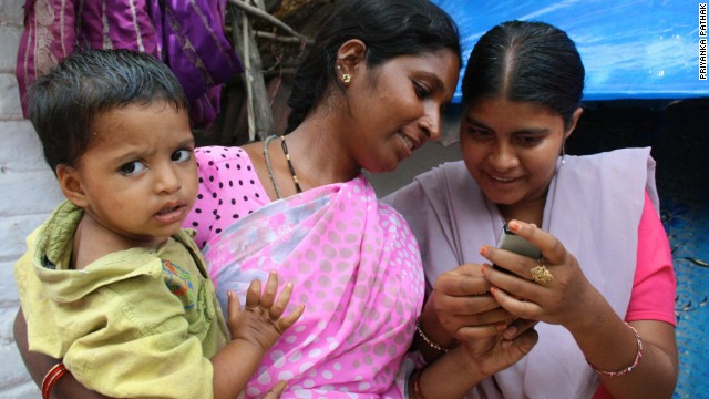 Two women in India using a mobile-based reminder system for vaccinations.