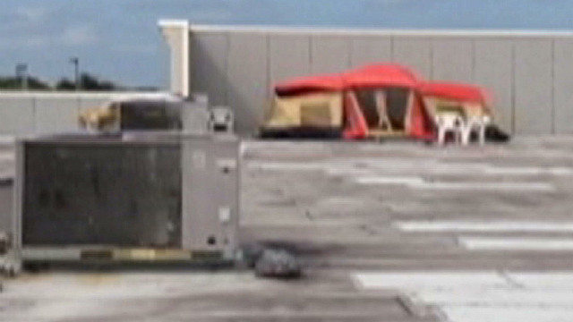 2 men are arrested after camping out on top of a business