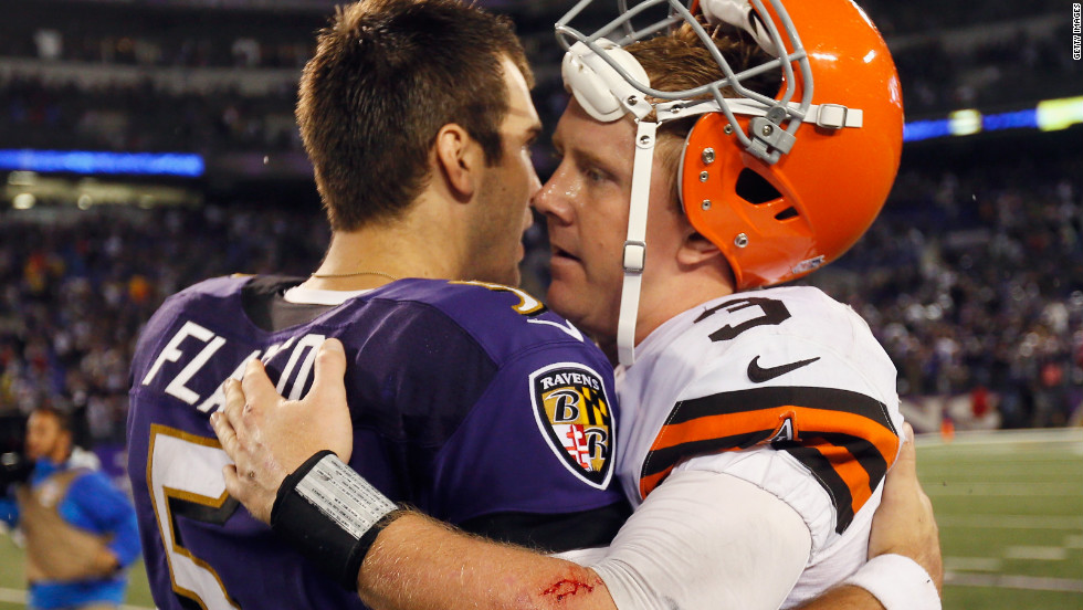 Baltimore Ravens quarterback Joe Flacco, left, hugs Cleveland quarterback Brandon Weeden following the Ravens' win on Thursday.