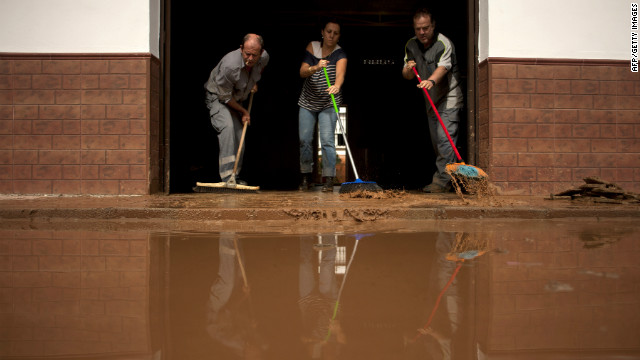 People clean the entrance of their flooded home in Bobadilla, near Malaga, southern Spain on September 29, 2012.